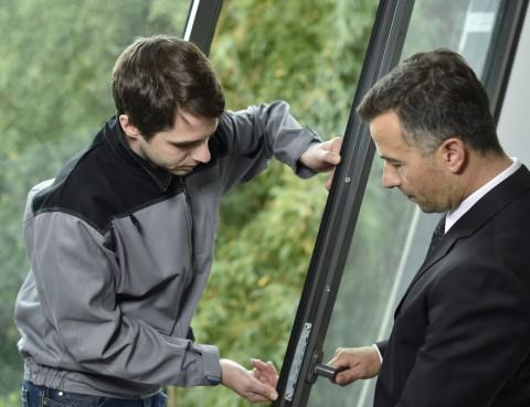 two men installing a screen door